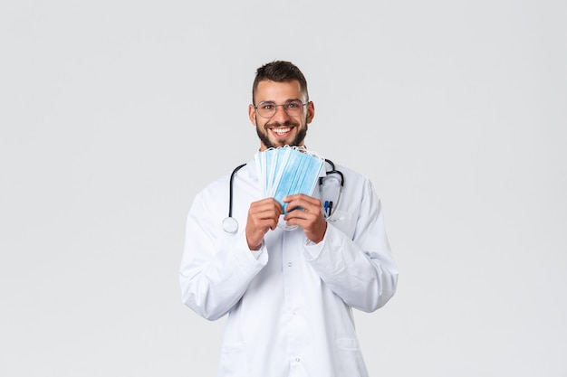 Travailleurs de la santé, assurance médicale, concept de pandémie et de covid-19. heureux beau docteur en lunettes et gommages, montrant des masques médicaux et souriant, recommande de se protéger pendant la couronne