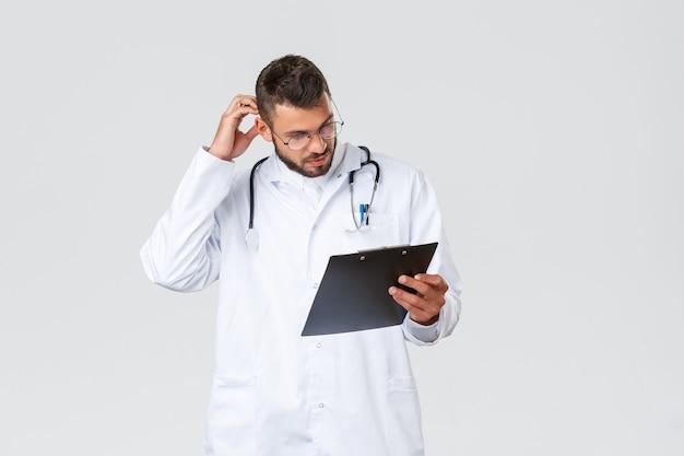 Travailleurs de la santé, assurance médicale, laboratoire de la clinique et concept covid-19. jeune médecin réfléchi en gommages, lunettes, étudiant le dossier du patient, gratter la tête et regarder le presse-papiers, lire des papiers.