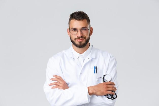 Travailleurs de la santé, coronavirus, pandémie de covid-19 et concept d'assurance. beau docteur déterminé, médecin en gommages et lunettes, poitrine croisée, stéthoscope, l'air confiant