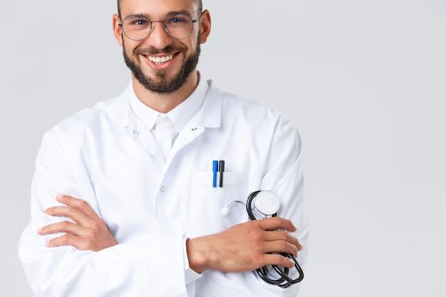Travailleurs de la santé, coronavirus, pandémie de covid-19 et concept d'assurance. gros plan sur un beau médecin de sexe masculin souriant en blouse blanche, lunettes, bras croisés sur la poitrine et tenez le stéthoscope, parlez aux patients