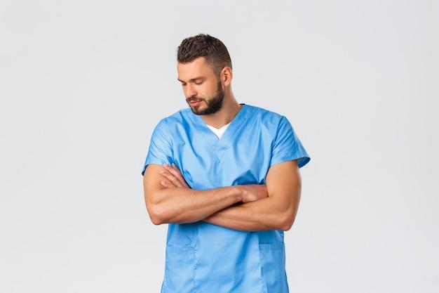 Travailleurs de la santé, médecine, covid-19 et concept d'auto-quarantaine pandémique. docteur fort et beau réfléchi, infirmier en gommage, poitrine croisée et regarde vers le bas, travaillant pendant le coronavirus.