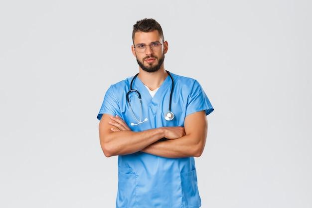 Travailleurs de la santé, médecine, covid-19 et concept d'auto-quarantaine pandémique. infirmier sérieux et déterminé, médecin en gommage bleu et stéthoscope, apparence professionnelle et confiante, poitrine à bras croisés