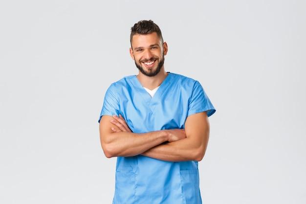 Travailleurs de la santé, médecine, covid-19 et concept d'auto-quarantaine pandémique. souriant beau, médecin hispanique, infirmier en gommage bleu, poitrine croisée, appareil photo riant gai.