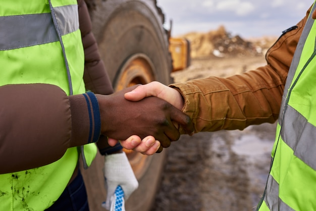 Travailleurs se serrant la main à l'extérieur gros plan
