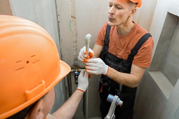 Les travailleurs soudent des tuyaux muraux pour une douche intégrée