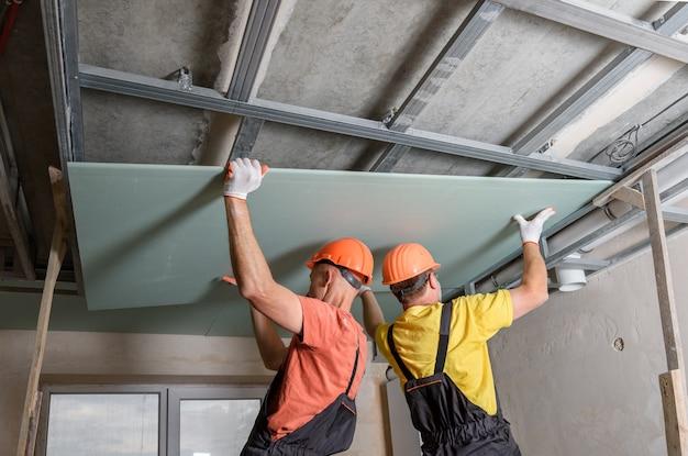 Les travailleurs soulèvent des plaques de plâtre pour les fixer davantage au plafond