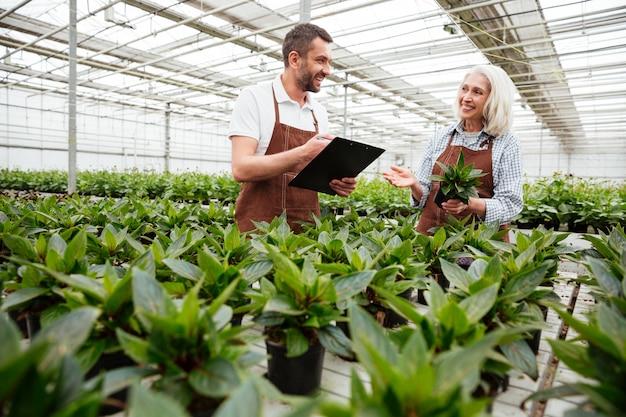 Travailleurs souriants dans le jardin à la recherche et au toucher des plantes