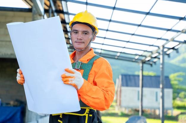 Travailleurs techniques professionnels travaillant avec des plans sur le chantier de construction