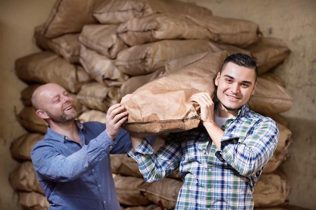 Travailleurs transportant des sacs de ciment