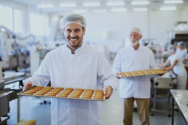 Travailleurs d'usine alimentaire en uniformes stériles portant des plateaux avec des biscuits. mise au point sélective sur les jeunes travailleurs.