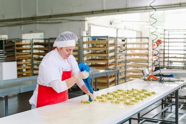 Les travailleurs de l'usine de confiserie préparent des desserts fourrés