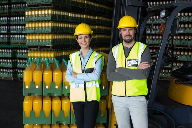 Travailleurs d'usine debout avec les bras croisés en usine