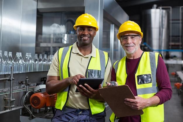 Travailleurs d'usine avec presse-papiers et tablette numérique travaillant dans l'usine