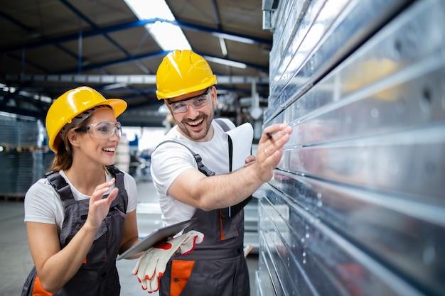 Travailleurs d'usine vérifiant la qualité des produits métalliques dans l'usine de production
