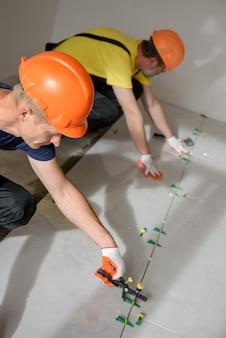 Les travailleurs utilisent des pinces et des coins en plastique pour niveler le grand carreau de céramique sur le sol
