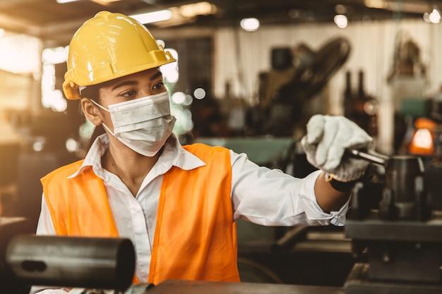 Travailleuse asiatique avec casque de sécurité et masque facial travaillant comme main-d'œuvre dans une usine de l'industrie lourde.