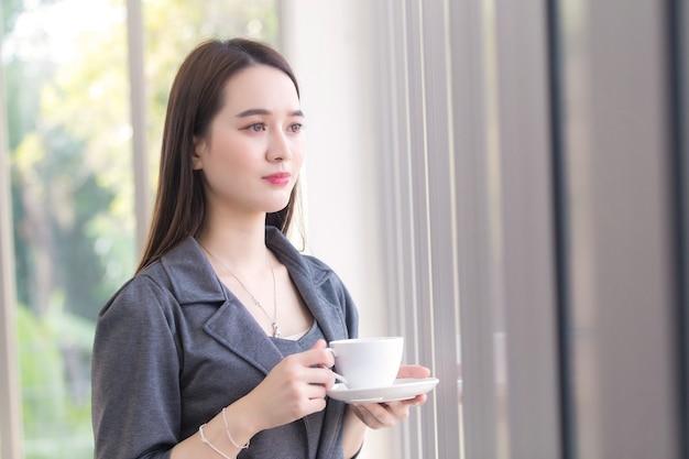 Une travailleuse asiatique regarde par la fenêtre pour penser à quelque chose tout en tenant une tasse de café dans sa main.