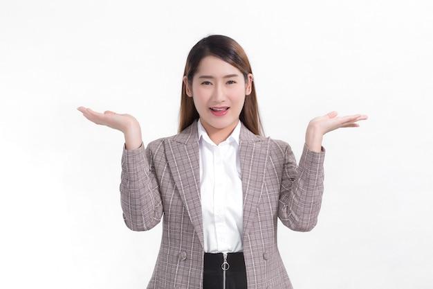 Une travailleuse asiatique sourit et montre ses mains pour présenter quelque chose sur le fond blanc.