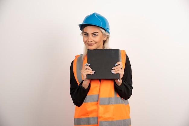 Travailleuse blonde avec ordinateur portable posant sur fond blanc. photo de haute qualité