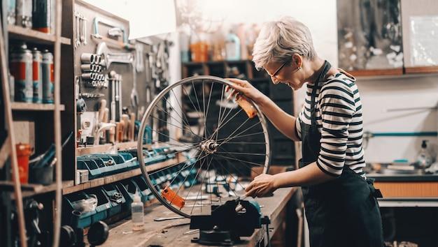 Travailleuse caucasienne mignonne tenant et réparant la roue de bicyclette en se tenant debout dans l'atelier de vélo.
