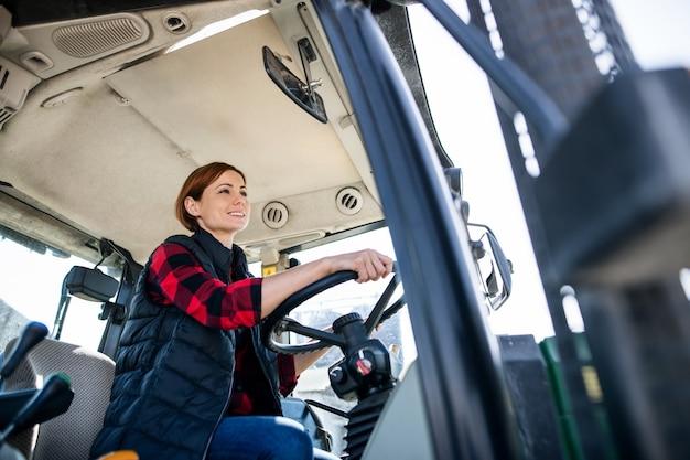 Une travailleuse chevauchant un tracteur sur une ferme de journal, l'industrie agricole.