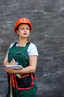 Travailleuse en combinaison avec ceinture à outils posant près de mur gris