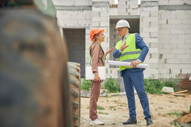 Travailleuse communiquant avec un ingénieur civil sur un chantier