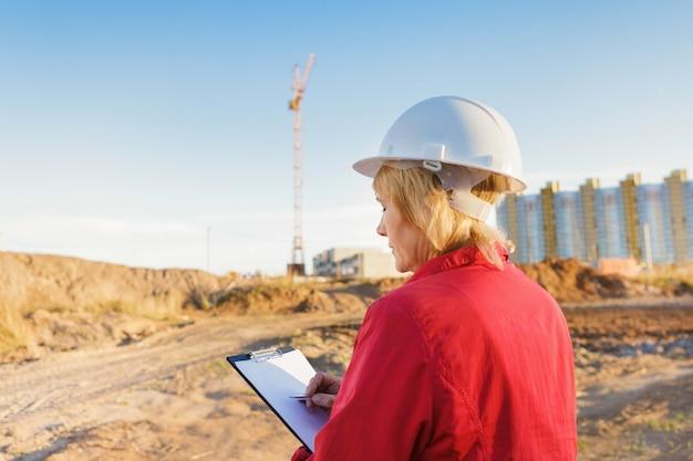 Une travailleuse de la construction est sur un chantier de construction. une femme d'âge moyen portant un casque blanc avec une tablette inspecte le territoire.
