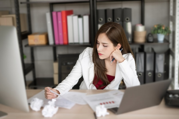 La travailleuse en costume blanc réfléchit à un nouveau projet.