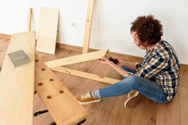 Une travailleuse dans la rénovation de l'atelier de menuisier. photo de haute qualité