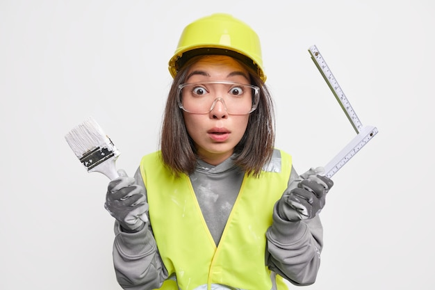 Une travailleuse du bâtiment surprise occupée à rénover sa maison tient un pinceau et un ruban à mesurer porte des lunettes de sécurité et un uniforme isolé sur blanc
