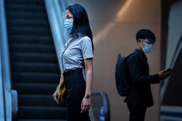 Travailleuse, elle est au métro. elle porte un écran facial et un masque anti-virus.