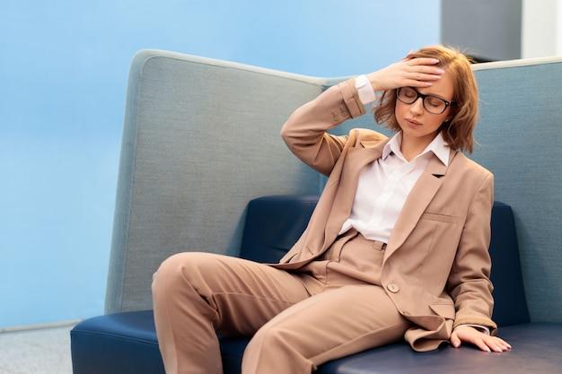 Travailleuse épuisée ayant une forte tension ou des migraines, ressentant une pression, tenant la main sur le front, assis sur un canapé