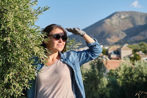Travailleuse d'une ferme d'oliviers, fond d'oliviers dans les montagnes