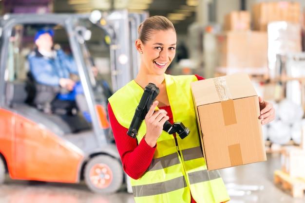 Travailleuse avec gilet de protection et scanner, détient un colis, se tenant devant l'entrepôt de la société de transport,