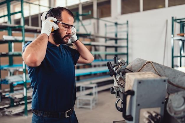 Travailleuse de machine à scier à ruban mettant des cache-oreilles protecteurs