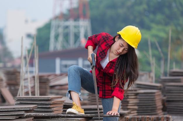 Travailleuse ouvrière sciant du bois en chantier, concept de la fête du travail