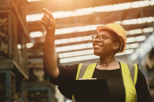 Une travailleuse professionnelle africaine noire compte de travail heureux vérifiant le contrôle des stocks de production d'inventaire dans l'industrie de l'usine d'affaires entrepôt waring ingénieur costume et casque pour la sécurité