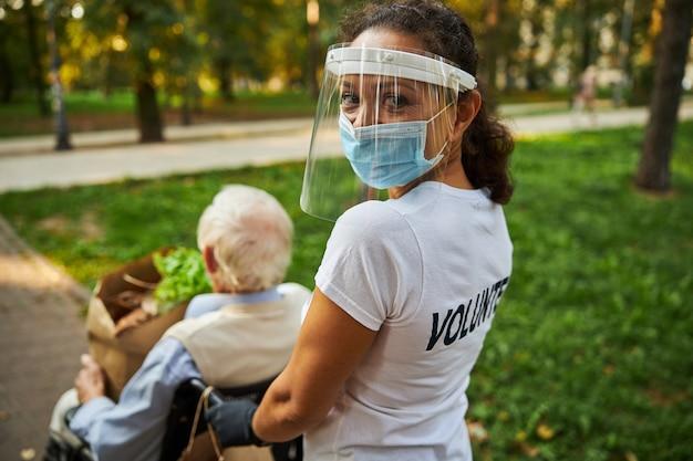 Une travailleuse sociale souriante regardant l'appareil photo dans le parc