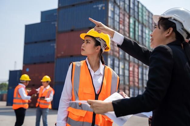 Travailleuse travaillant avec foreman, debout avec un casque jaune pour contrôler le chargement et vérifier la qualité des conteneurs du cargo cargo pour l'importation et l'exportation au chantier naval ou au port