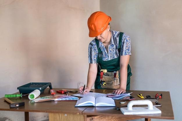 Travailleuse en uniforme de protection avec des outils de peinture