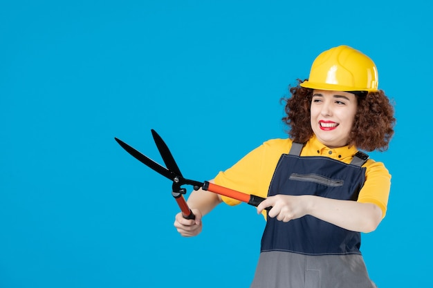 Travailleuse en uniforme avec sécateur sur bureau bleu