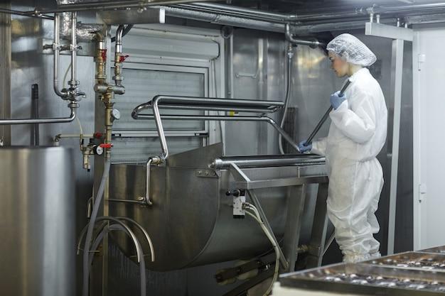 Travailleuse de vue grand angle utilisant un mélangeur dans une usine de production d'aliments propres, espace de copie