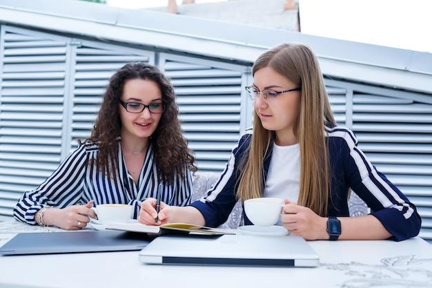 Des travailleuses souriantes et prospères travaillent ensemble, travaillent sur un ordinateur portable sur la terrasse, des collègues féminines sont occupées à discuter d'idées, des filles dans un café lors d'une réunion d'affaires. concept d'entreprise