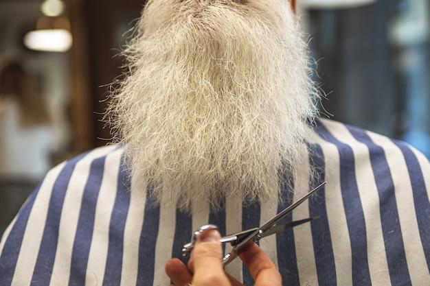 Travaillez dans les détails. homme de coiffeur coupe la barbe de senior avec des ciseaux