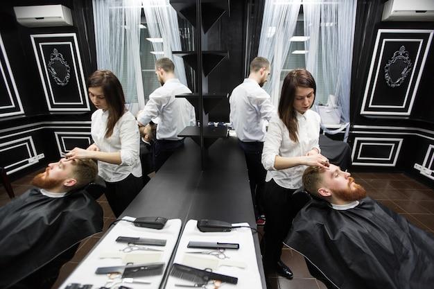 Travaillez dans un salon de coiffure. deux maîtres au travail.