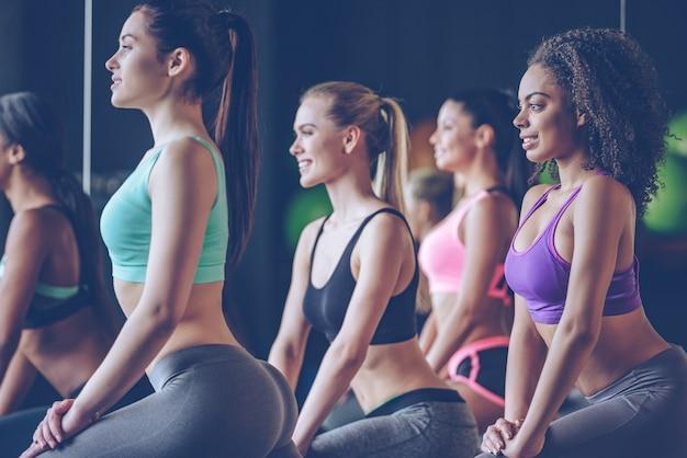 Travaillez les filles ! vue latérale de belles jeunes femmes avec des corps parfaits en vêtements de sport faisant de l'exercice avec le sourire au gymnase