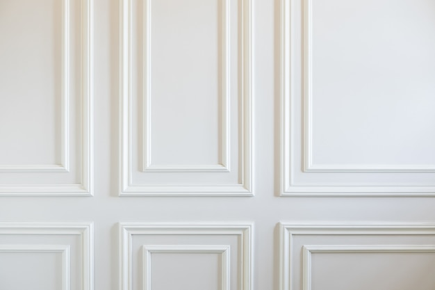 Travaux de finition - fragment de murs blancs classiques avec panneaux muraux installés et décoré de moulures. contexte