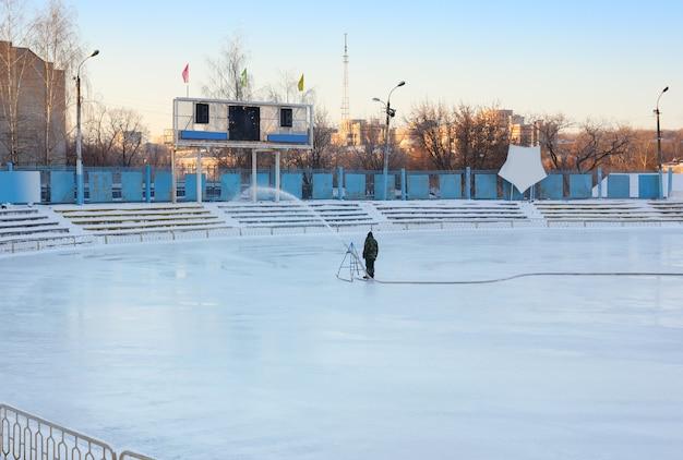 Travaux d'hiver pour remplir le stade d'eau. patinage
