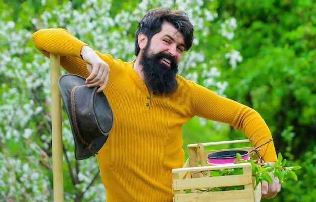 Travaux de jardinage au printemps, jardinier se préparant à la plantation, homme barbu avec des outils de jardinage.